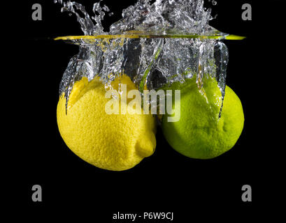 A lemon and a lime splashing into water on a black background. - Stock Image