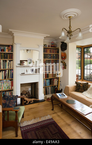 house interiors, small snug with bookshelves, of self-built house designed on arts and crafts design principles - Stock Image
