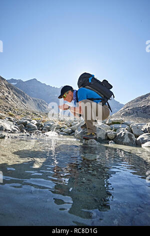 Hiker drinking from pool, Mont Cervin, Matterhorn, Valais, Switzerland - Stock Image