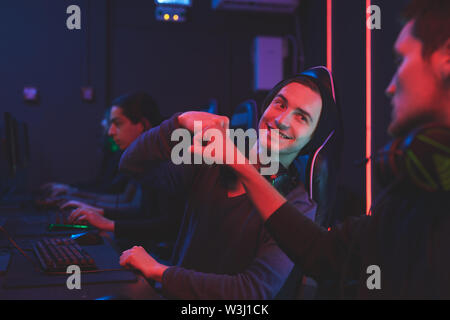 Team of computer gamers sitting at table and making fist bump while celebrating win in computer club - Stock Image