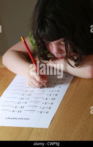 Little girl doing maths homework - Stock Image