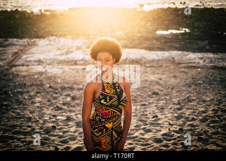 Attractive young african style ethnic dress and hair traditional girl pose at the outdoor beach with golden sun light in background - smiling and look - Stock Image