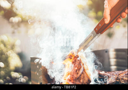 Man chef grilling beef steak at barbecue dinner party outdoor - Close up male hand cooking meat on bbq for family in the garden - Stock Image