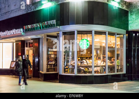 Evening at Lincoln Road Mall Starbucks Coffee shop with people seated drinking coffee inside and a couple walking - Stock Image