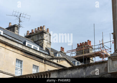 A rooftop in the city of Bath with TV ariels and scaffolding around a chimney stack with multiple chimney pots - Stock Image