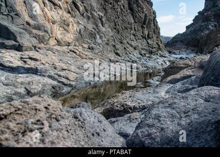 Reflections in rock pools of the volcanic coastline of La Palma Island - Stock Image