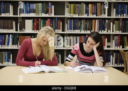A young women studying in a library while her friend checks her mobile phone - Stock Image