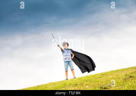 Proud young boy playing the super hero wearing a homemade cloak and brandishing a toy sword on the skyline against a blue sky - Stock Image