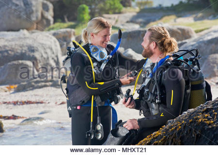 Couple in wetsuits going ocean scuba diving from rocky beach and checking equipment - Stock Image