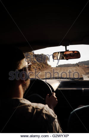 Motoring on unsurfaced roads, showing the view through the windscreen, on Kea island, Greece. - Stock Image