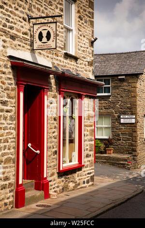 UK, Cumbria, Sedbergh, Main Street, Clutterbucks and Clobber Community Charity Shop on corner of New St - Stock Image