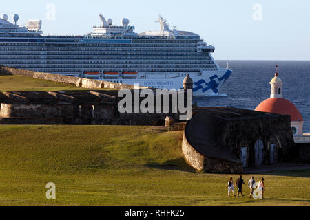 A cruise ship sails out of the harbor past Castillo San Felipe del Morro, Old San Juan, Puerto Rico - Stock Image