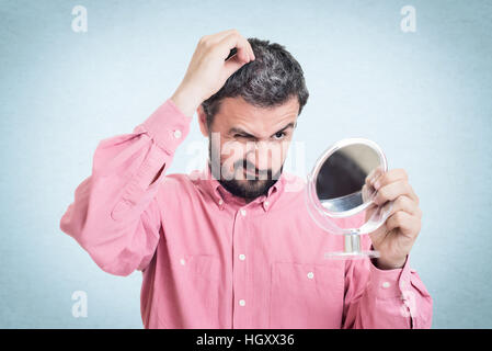 Horrified young man looking in the mirror at the first grey hair on his scalp - Stock Image