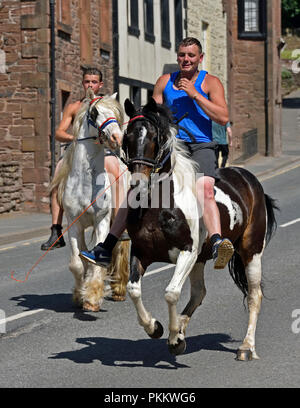 Two Gypsy Travellers riding horses at Appleby Horse Fair 2018. The Sands, Appleby-in-Westmorland, Cumbria, England, United Kingdom, Europe. - Stock Image