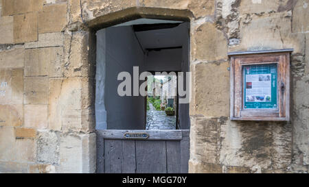 Cotswold limestone surrounds a half doored arched alleyway between terraced houses in the picturesque market town high street of Chipping Campden - Stock Image