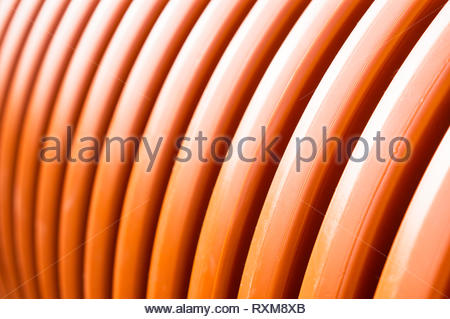 Close up of a plastic orange background with curvy lines. - Stock Image