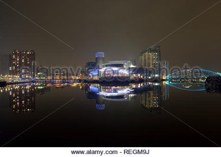 Modern cityscape panorama at night. Lit buildings reflect off calm water - Stock Image