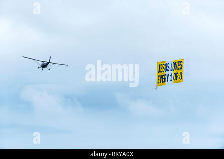 A small aeroplane towing a banner with a religious message. - Stock Image