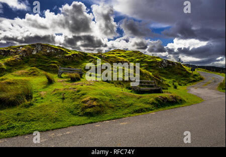 Two Weathered Wooden Benches Beneath The Street In The Village Of Drumbeg In Scotland - Stock Image