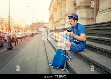 Man tourist backpack and photo camera on film looking at map and phone in old city - Stock Image
