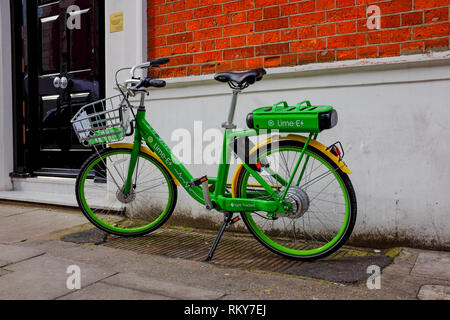 A Lime E electric bike stands on the pavement in central London in February 2019. - Stock Image