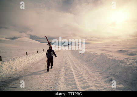 Rear view of man walking on snowy landscape against cloudy sky - Stock Image
