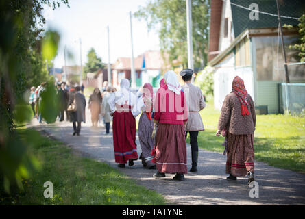 People in traditional Russian clothes walk between wooden houses - midle shot - Stock Image