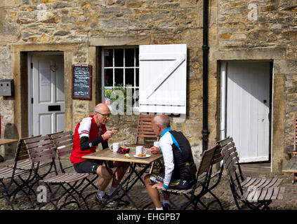 Cyclists outside cafe in village of Slaidburn in the Forest of Bowland (AONB), Ribble Valley district of Lancashire, - Stock Image