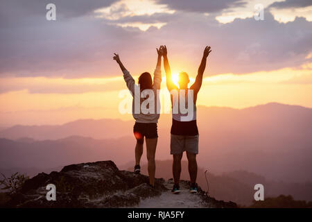 Happy couple with raised arms stands on mountain top against sunset and having fun in winner pose - Stock Image