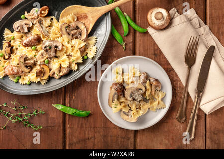Mushroom and cheese pasta. Farfalle with cremini and green peas, shot from above with ingredients on a dark rustic wooden background - Stock Image