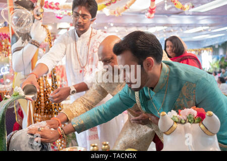 A teenage pandit and two devout worshippers pour milk over and touch a Shiva Lingam at a Hindu temple in Jamaica, Queens, New York. - Stock Image