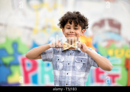 Proud young boy with a beaming smile and unruly curly dark hair pulling on a gold bow tie around his neck in front of a colorful graffiti wall - Stock Image