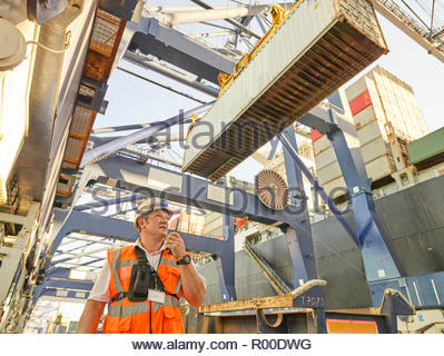 Dock manager communicating with crane driver to load cargo to lorry - Stock Image