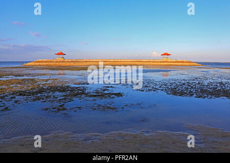 Balinese Pagodas on Karang beach at Sanur, Bali, Indonesia. Taken late afternoon at low tide with seaweed and sand. - Stock Image