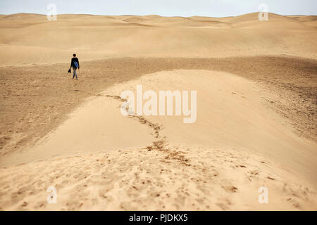 Mature female tourist walking barefoot on sand dune, rear view, Las Palmas, Gran Canaria, Canary Islands, Spain - Stock Image
