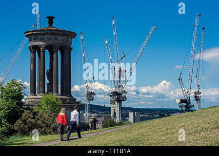 A couple walk by the Dugald Stewart Monument on Calton Hill, Edinburgh. In the background are cranes working on the St James Project. - Stock Image