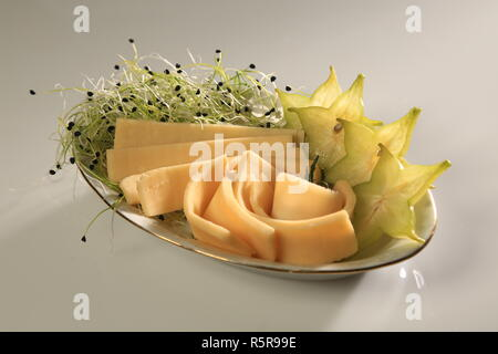 Slices of chhese with slices of starfruit and sprouts on the side. - Stock Image