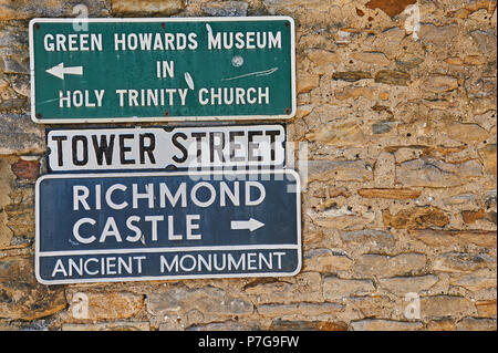 Signs on a stone wall in Richmond North Yorkshire. - Stock Image
