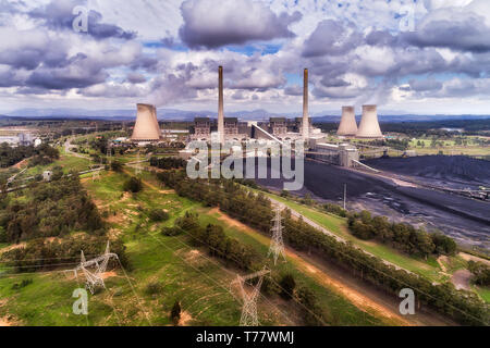 Power lines transmitting electricity away from Bayswater power statiion burning fossil black coal fuel in the middle of Hunter Valley, Australia NSW. - Stock Image