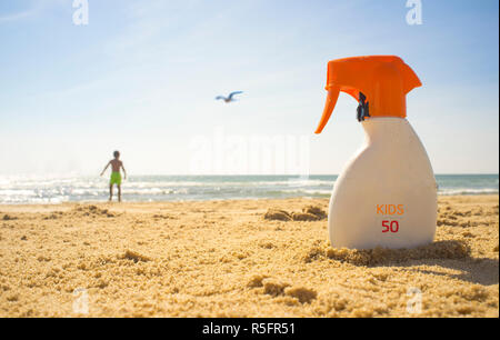 Sunblock cream with Sun Protection Factor or SPF 50 on beach sand. Child boy on background - Stock Image