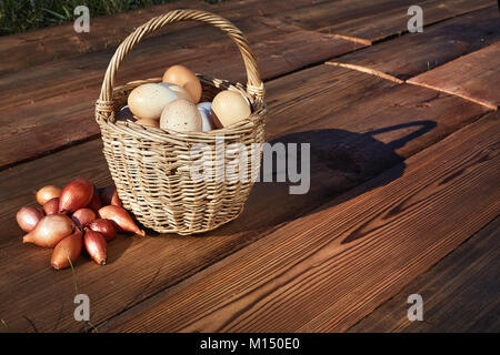 Home Chicken eggs in basket on rustic wooden background. A bunch of small onions - Stock Image