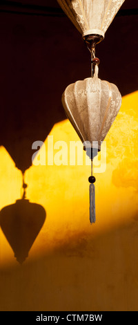 Two cream ivory colored silk lanterns on an ochre wall, Hoi An, Viet Nam - Stock Image