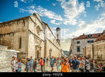 Crowds of tourists walk the main street or stradun next to St Saviour Church in the ancient walled city of Dubrovnik, Croatia - Stock Image