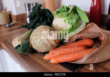 Lovcally bought fresh vegetables from Sussex cauliflower carrots in brown paper bag leeks celeriac and broccoli bought loose ready for cooking - Stock Image