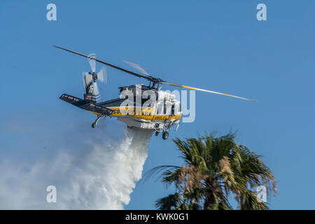 Los Angeles County Fire Department Air 16 doing a water drop on a brush fire. - Stock Image