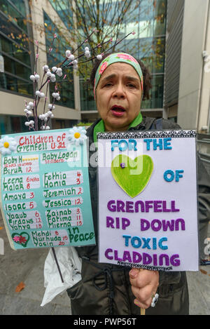 London, UK. 17th October 2018. A woman who grew up close to Grenfell and worked there as a nursery nurse holds placards at the protest outside the Ministry of Housing, Communities and Local Government by residents living in tower blocks covered in Grenfell-style cladding, Fuel Poverty Action, and Grenfell campaigners demanding that the government make all tower-block homes safe and warm. Credit: Peter Marshall/Alamy Live News - Stock Image