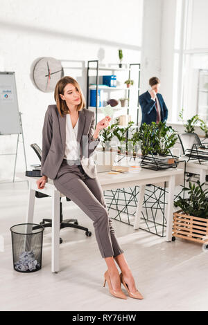 selective focus of woman holding sticky note with later lettering while standing near desk with coworker on background, procrastination concept - Stock Image
