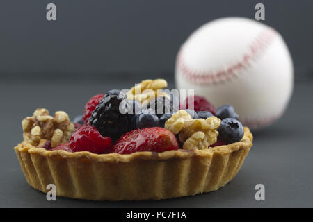 Healthy lifestyle choices reflected in fruits and nuts among food choices and activities like baseball.  Symbols placed on dark background. - Stock Image