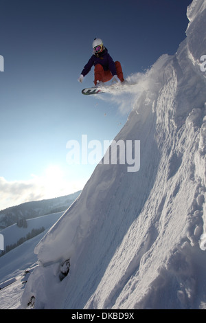 Snowboarder jumping down mountain - Stock Image