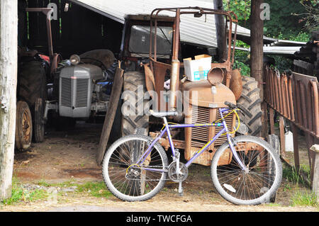 Collection of old tractors, implements and tools in a covered leanto with a modern bicycle in the foreground. Purbeck, Dorset - Stock Image